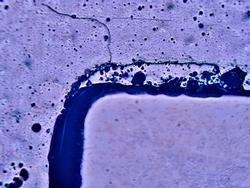 Das Bild zeigt ein OCR mit deutlichen Qualitätsunterschieden im verklebten Bereich (dunkler Balken). Die ungeraden, zackigen bzw. welligen Konturen werden den Delaminationsprozess ermöglichen.