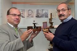 Dr. Wolfgang Wimmer (links), Leiter des ZEISS-Archivs nimmt ein historisches Mikroskop aus dem Jahr 1850 von Manfred Eichel entgegen. Foto: Jürgen Scheere/ZEISS
