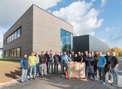 Die Geschäftsführung und Mitarbeiter der primeLine Unternehmensgruppe vor dem neuen Firmengebäude.